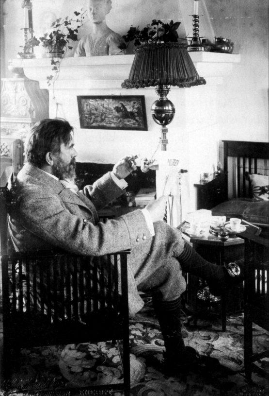 En ældet P.S. Krøyer med cigar, læsende i dagligstuen